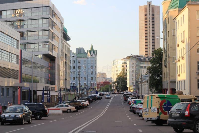 Een straat van Moskou in de zomer met vele gebouwen en geparkeerde auto s