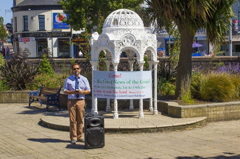 Een Straatprediker Neer predikend het goede nieuws van redding door geloof alleen in Jesus Christ in Gedaald Co van Tuinenbangor stock afbeelding