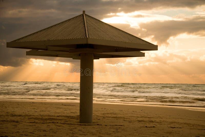 Een strand met een parasol op zonsondergang stock foto