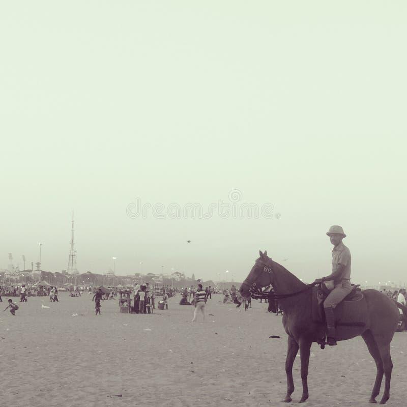 Een strandpolitieagenten op horseback stock afbeeldingen