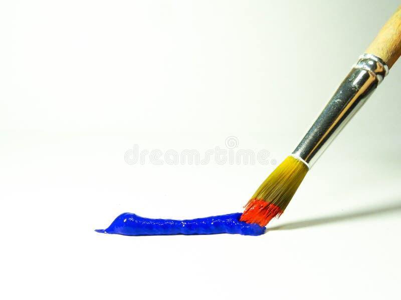 Een strook van blauwe verf en een borstel met rode verf royalty-vrije stock foto