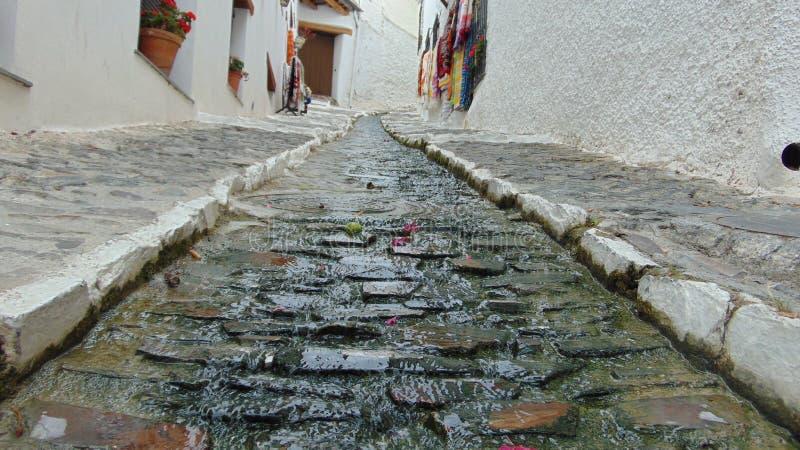 Een stroom die door een kleine steeg in een Spaanse bergstad vloeien royalty-vrije stock foto's