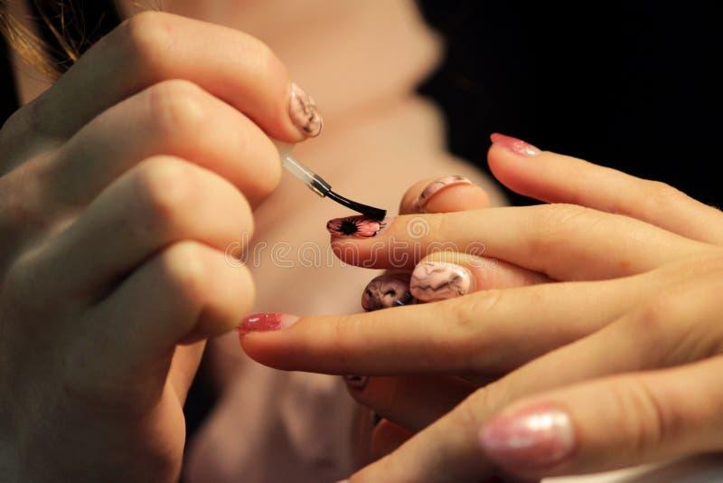Een student bij de trainingscursussen van manicure bereidt de hand van de cliënt voor alvorens schellak toe te passen toepassing  stock fotografie