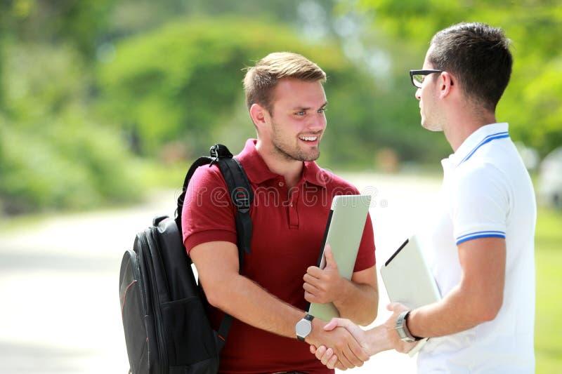 Een student gelukkig om zijn vriend te ontmoeten en dan handen te schudden stock afbeeldingen