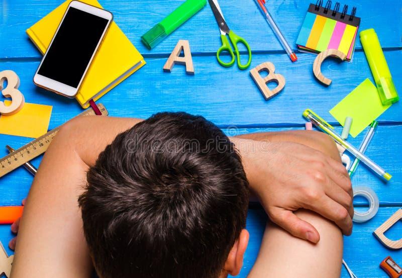 Een student is in slaap in de werkplaats, knoeit creatief De student is lui en wil niet leren De kerel is vermoeid en in slaap stock foto's