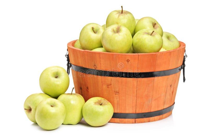 Een studio die van groene appelen in een houten mand is ontsproten stock afbeeldingen