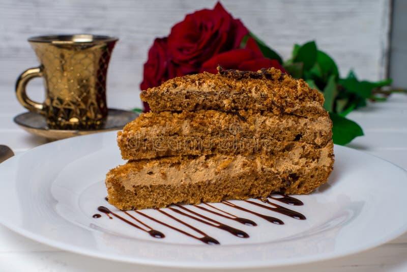 Een stuk cake, witte kop thee en aardbeien Selectieve nadruk stock foto