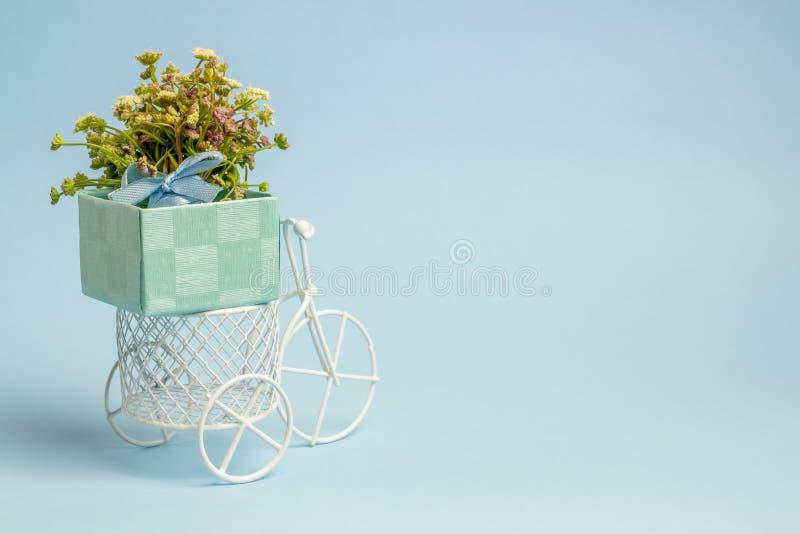 Een stuk speelgoed fiets draagt bloemen Het idee voor een prentbriefkaar Achtergrond voor een uitnodigingskaart of een gelukwens  stock afbeeldingen