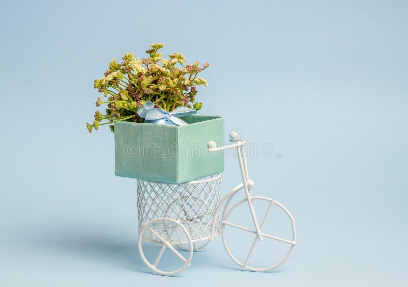 Een stuk speelgoed fiets draagt bloemen Het idee voor een prentbriefkaar Achtergrond voor een uitnodigingskaart of een gelukwens  royalty-vrije stock afbeeldingen