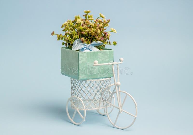 Een stuk speelgoed fiets draagt bloemen Het idee voor een prentbriefkaar Achtergrond voor een uitnodigingskaart of een gelukwens  stock afbeelding