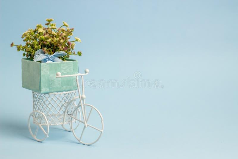 Een stuk speelgoed fiets draagt bloemen Het idee voor een prentbriefkaar Achtergrond voor een uitnodigingskaart of een gelukwens  royalty-vrije stock foto's