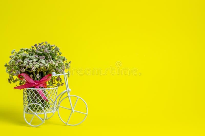 Een stuk speelgoed fiets draagt bloemen Het idee voor een prentbriefkaar Gele achtergrond minimalism stock afbeeldingen