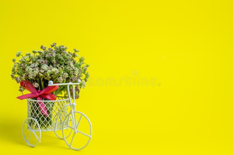 Een stuk speelgoed fiets draagt bloemen Het idee voor een prentbriefkaar Gele achtergrond minimalism royalty-vrije stock foto
