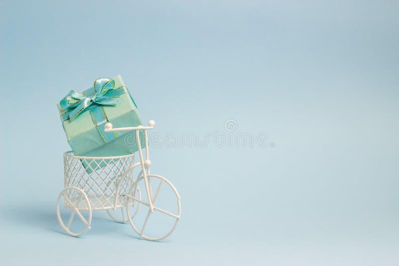 Een stuk speelgoed fiets draagt een gift Het idee voor een prentbriefkaar Achtergrond voor een uitnodigingskaart of een gelukwens stock foto
