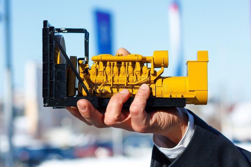Een stuk speelgoed model van een reeks van de gasgenerator is in de mannelijke hand stock foto's