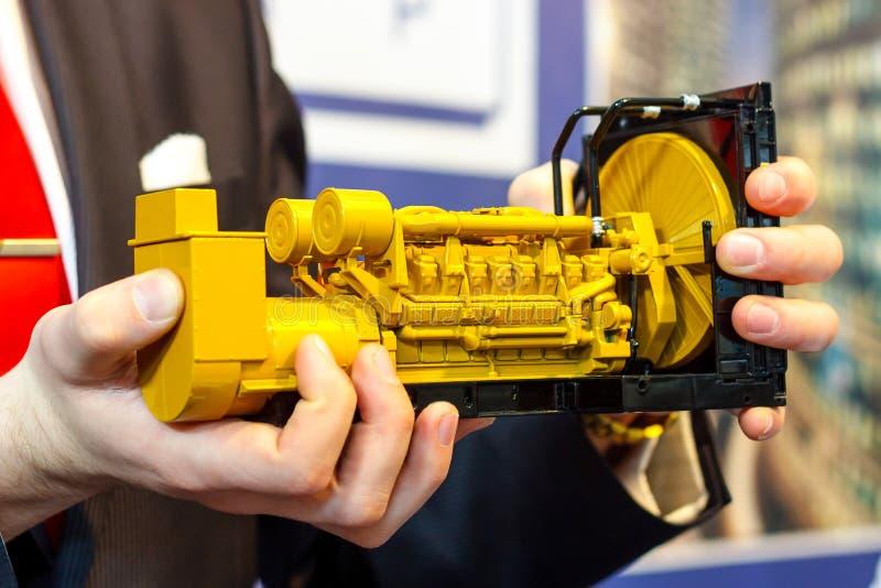 Een stuk speelgoed model van een reeks van de gasgenerator is in de mannelijke hand stock afbeeldingen