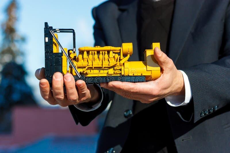 Een stuk speelgoed model van een reeks van de gasgenerator is in de mannelijke hand royalty-vrije stock afbeeldingen