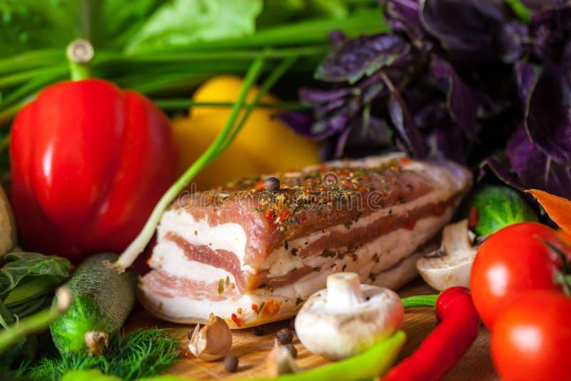Een stuk van bacon met kruiden en groenten stock foto's
