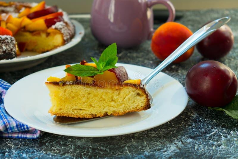 Een stuk van cake met perziken en pruimen met een blad van munt op een plaat worden verfraaid die Het voorbereiden van een disser stock afbeeldingen