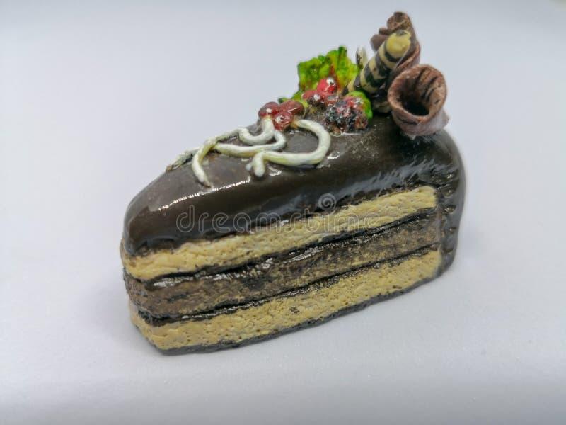 Een stuk van chocoladecake dat ik van polymeerklei maakte, gebakken dan verf eindigt met glanzende verbinding om een realistische royalty-vrije stock afbeelding