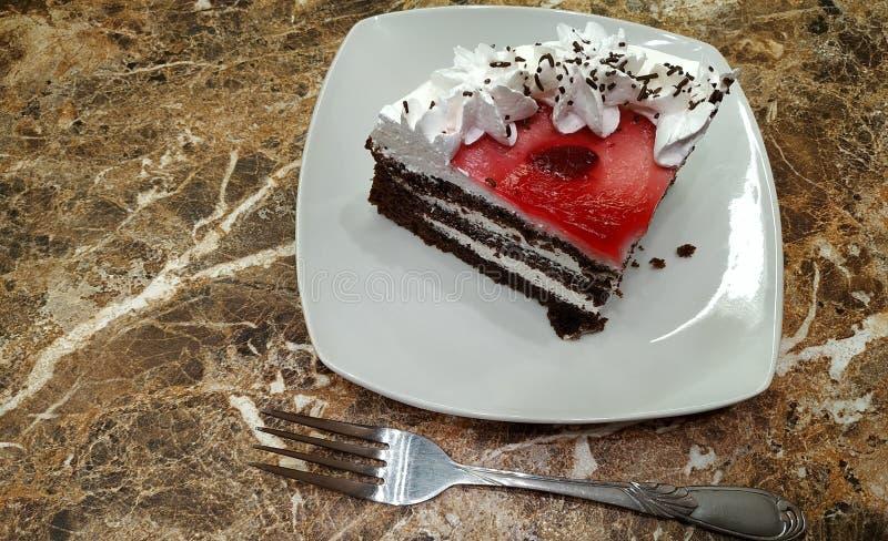 Een stuk van chocoladecake op een plaat en een vork op een marmeren lijst Close-up stock afbeelding