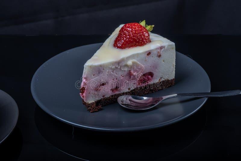 Een stuk van de cake van het roomfruit met aardbeien op een zwarte glaslijst die wordt verfraaid stock fotografie