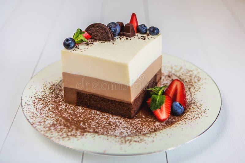 Een stuk van een moussecake drie chocolade bevindt zich op een plaat die, met geraspte chocolade wordt bestrooid, en verfraaide m stock afbeelding