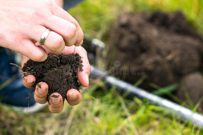 Een stuk van grond in de handen van de sterke mensenlandbouwer royalty-vrije stock foto's