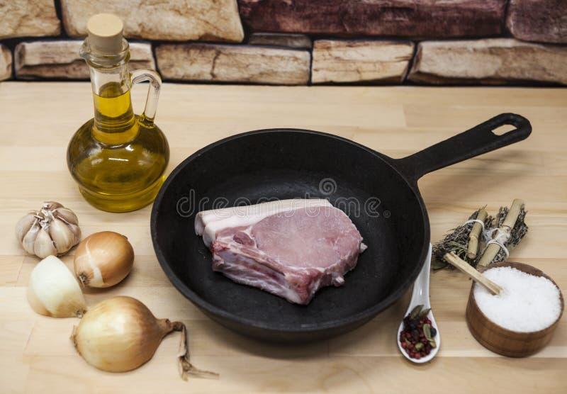 Een stuk van heerlijk vers ruw varkensvleesclose-up op een gietijzerpan, uien, knoflook, kruiden, zout, olijfolie op rustieke keu stock foto's