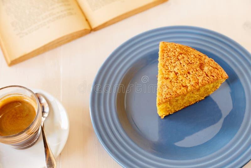 Een stuk van heerlijke wortelpastei op een blauwe glanzende plaat en een uitstekend oud boek Een deel van een eigengemaakte cupca stock foto's