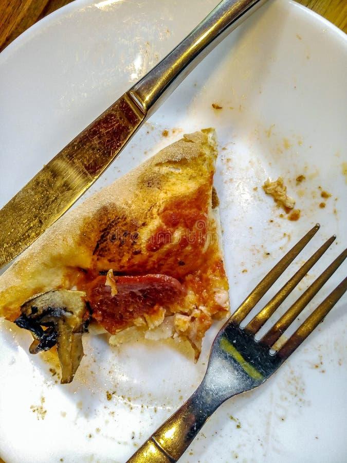 Een stuk van helft-gegeten pizza legt op een witte plaat naast vork en mes, hoogste mening royalty-vrije stock foto