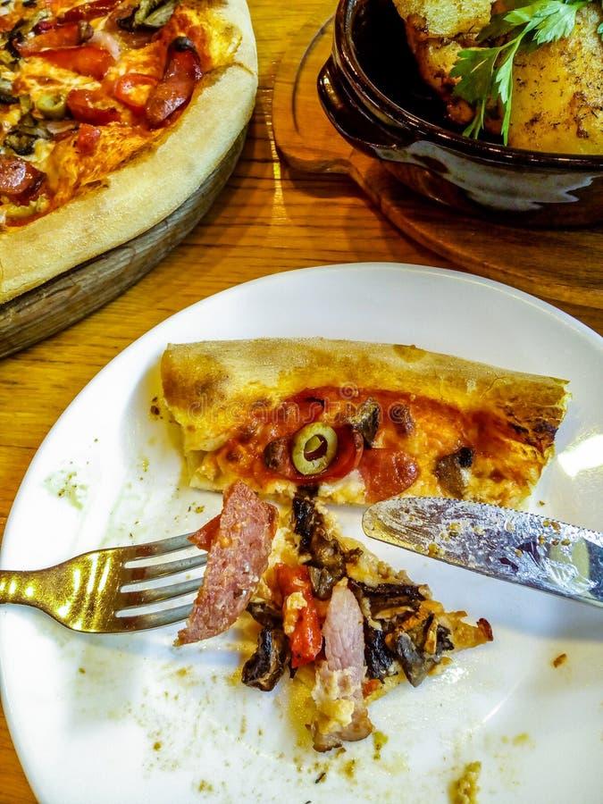 Een stuk van helft-gegeten pizza op een witte plaat met vork en mes Houten plaat met een pizza en een kom van aardappelen in de s stock foto's