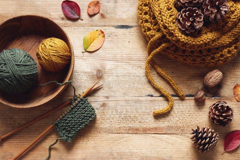 Een stuk van het breien met houten naalden en garen onder bladeren stock fotografie
