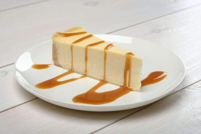 Een stuk van kaastaart, motregende in karamelsaus op een witte plaat die zich op houten witte lijst bevinden royalty-vrije stock afbeelding