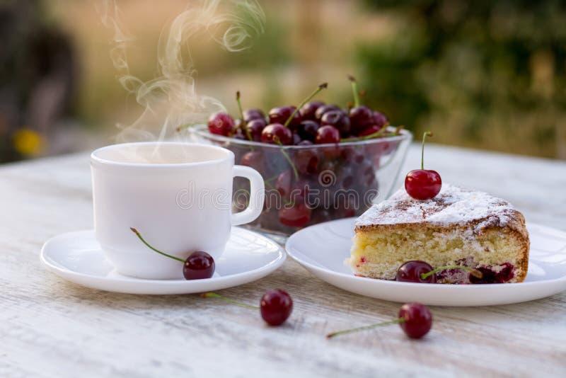Een stuk van kersenpastei en een hete thee met citroen royalty-vrije stock afbeelding