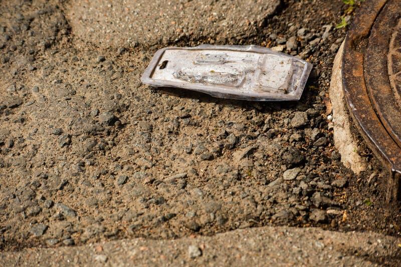 Een stuk van plastiek ligt op de oude weg en het mangat stock foto's