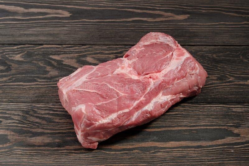 Een stuk van ruwe varkensvleeshals Varkensvleeshaasbiefstuk op papier op een donkere achtergrond royalty-vrije stock foto