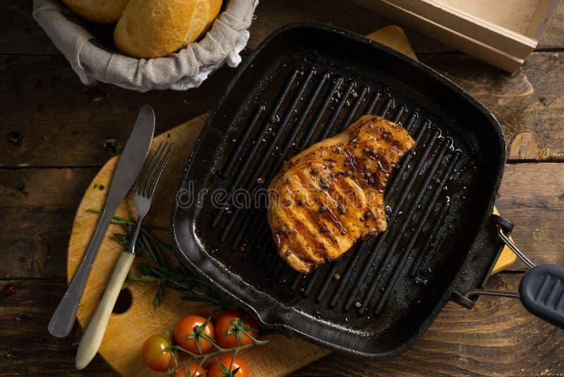Een stuk van vlees op de grill op houten lijst royalty-vrije stock fotografie