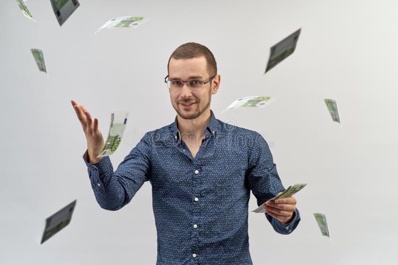 Een succesvolle jonge mens die in overhemd en glazen een pakje van contant geld houden en werpt het op rond zich stock foto