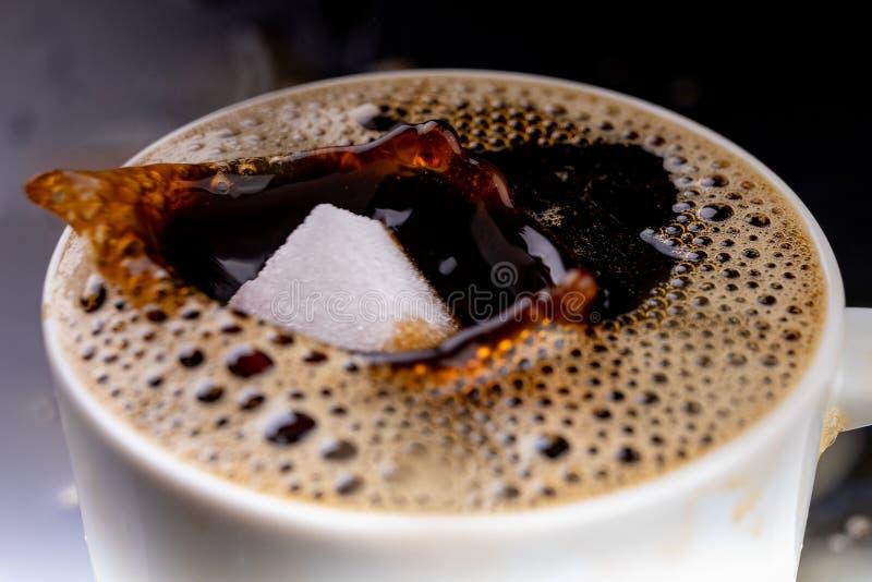 Een suikerkubus in een kop met zwarte koffie wordt gelaten vallen die Dalende suiker in een warme drank royalty-vrije stock afbeelding