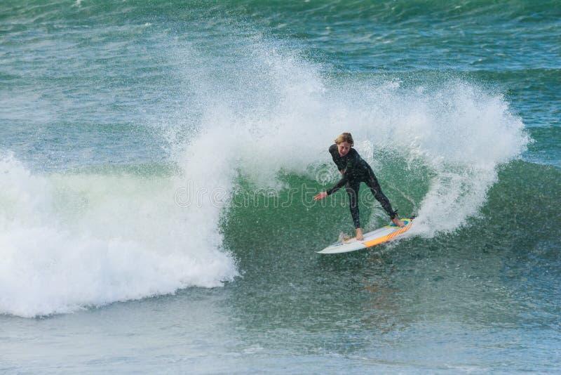 Een surfer die een beperking uitvoeren bij de bovenkant van een golf royalty-vrije stock fotografie
