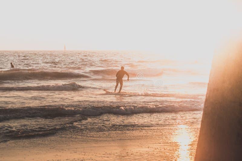 Een surfer die op het strand lopen stock afbeeldingen