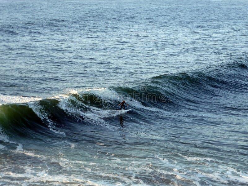 Een Surfer die een reusachtige golf berijden stock afbeelding