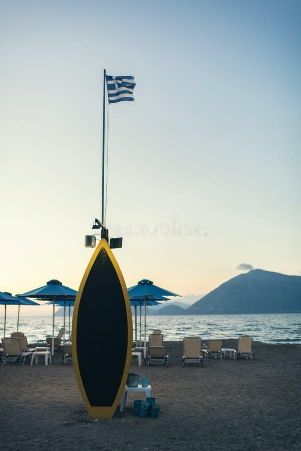 Een surfplank met Griekse vlag op het lege strand stock fotografie