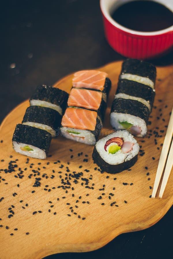 Een sushi met van het sauskom en bamboe stokken op de zwarte achtergrond op de houten raad wordt geplaatst die royalty-vrije stock foto's