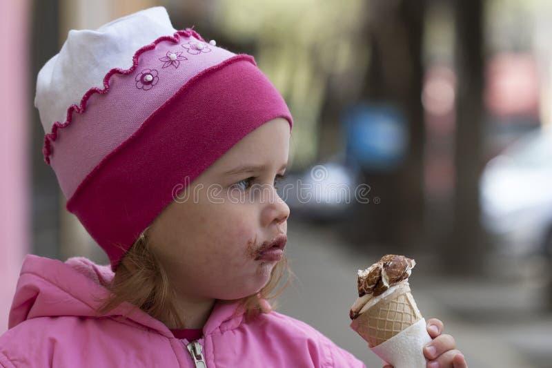 Een sweet-toothed jong meisje met roomijs en met smeary gezicht stock foto