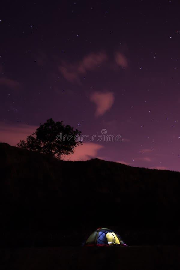 Een symbool van hoop eenzame gloeiende tent in de duisternis stock afbeeldingen