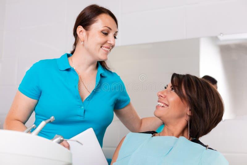 Een tandarts beëindigt een succesvolle tandrestauratie, adviseert een arts een gelukkige patiënt, een mooie langharige vrouw royalty-vrije stock fotografie