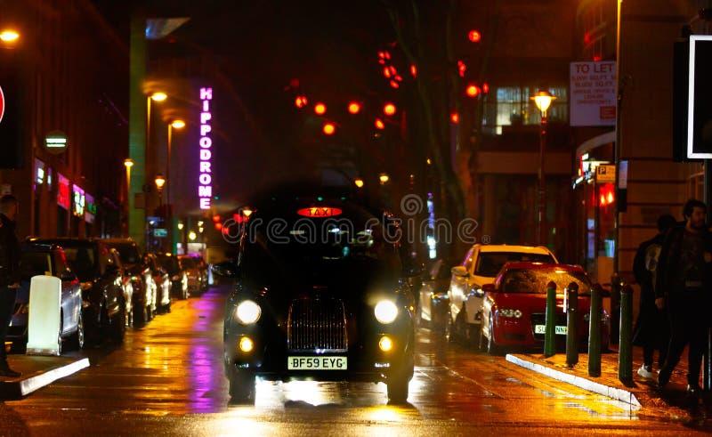 Een taxi van Londen wacht in een natte stadsscène stock afbeelding