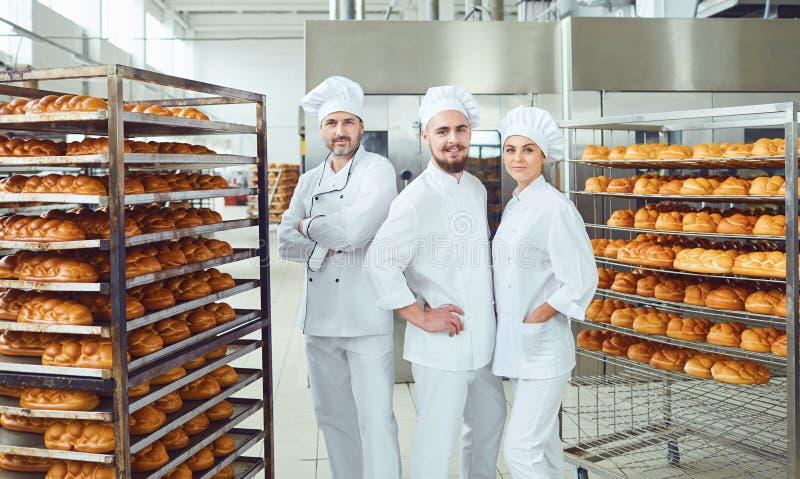 Een team van bakkers glimlacht bij de bakkerij royalty-vrije stock foto's